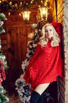 Moda mulher sexy loira de suéter vermelho, se divertindo e posando contra a árvore de natal e um poste de luz. árvore de inverno e natal em uma casa de vila. mulher com uma figura perfeita e um sorriso