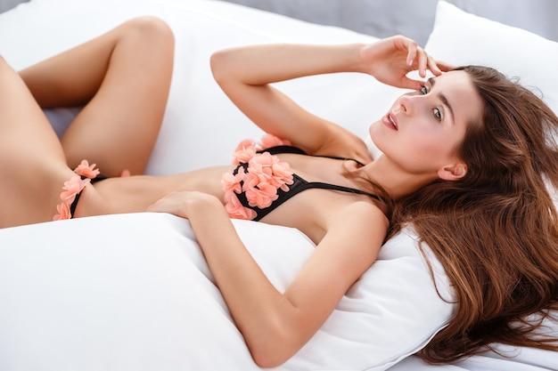Moda mulher verão. garota sexy e sorridente feliz com corpo em forma, pernas longas, pele saudável de biquíni