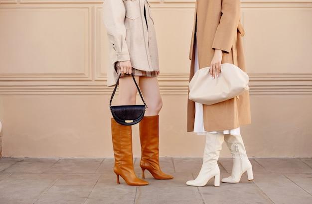 Moda outono duas mulheres com casaco de roupas da moda, botas de cano altas, bolsas. roupa estilo de rua