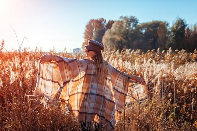 Moda outono. jovem mulher vestindo roupa elegante ao ar livre