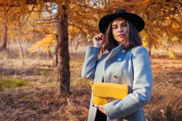 Moda outono. jovem mulher vestindo roupa elegante e segurando a bolsa ao ar livre
