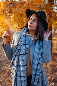 Moda outono. jovem mulher vestindo roupas elegantes no parque. roupas e acessórios