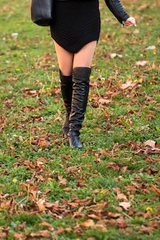 Moda outono, sapatos nas pernas da mulher em folhas no chão