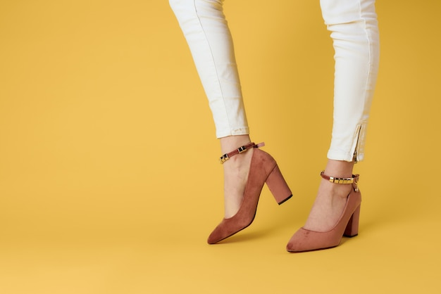 Moda pés femininos sapatos luxo fundo amarelo estilo elegante. foto de alta qualidade