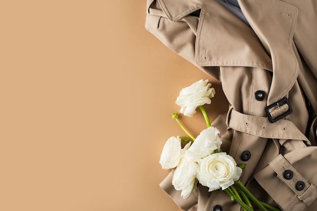 Moda plana leigos com casacos de trincheira e flores, conceito de primavera em fundo bege
