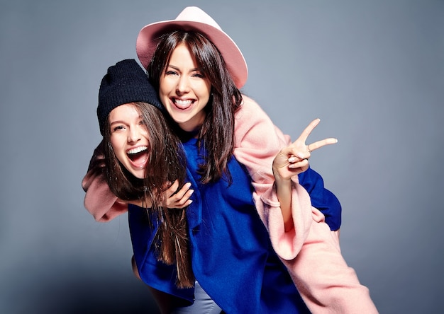 Moda retrato de dois modelos de mulheres morenas sorridentes em verão casual hipster casaco posando. meninas abraçadas nas costas