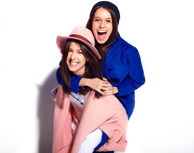 Moda retrato de dois modelos de mulheres morenas sorridentes no sobretudo casual hipster de verão isolado no branco. meninas abraçadas nas costas