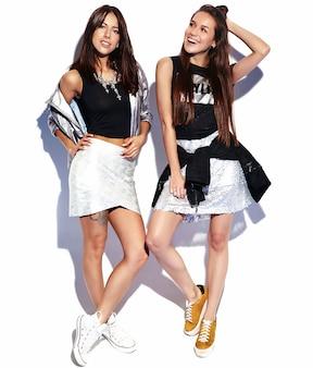 Moda retrato de duas modelos morenas sorridentes em roupas de verão casual hipster isoladas no branco. comprimento total
