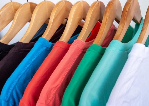 Moda t-shirt no cesto de roupas - close-up do armário colorido brilhante em cabides de madeira no armário da loja.