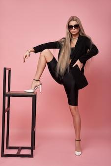 Moda uma mulher jovem e bonita elegante com uma jaqueta preta e óculos escuros posando em um fundo rosa encostado em uma cadeira
