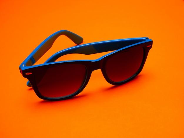 Moda verão conceito azul óculos de sol em uma mesa de laranja.