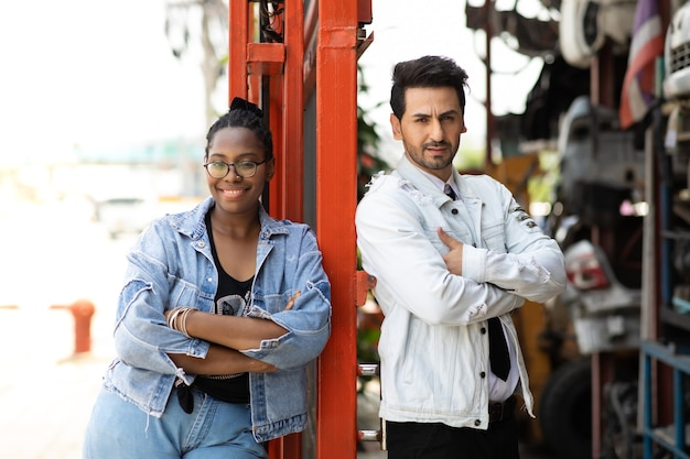 Modelagem de foto de retrato. afro-americana funcionária trabalhadora e gerente hispânico trabalhando juntos na velha loja de armazém de peças de automóveis e automóveis.
