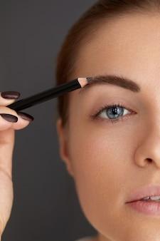 Modelagem de sobrancelhas. mulher jovem de beleza com lápis de sobrancelha. close da menina bonita com maquiagem profissional, contornando as sobrancelhas com lápis de sobrancelha.