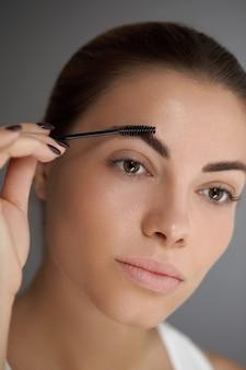 Modelagem de sobrancelhas. retrato de uma menina bonita com lápis de sobrancelha. close de jovem com maquiagem profissional