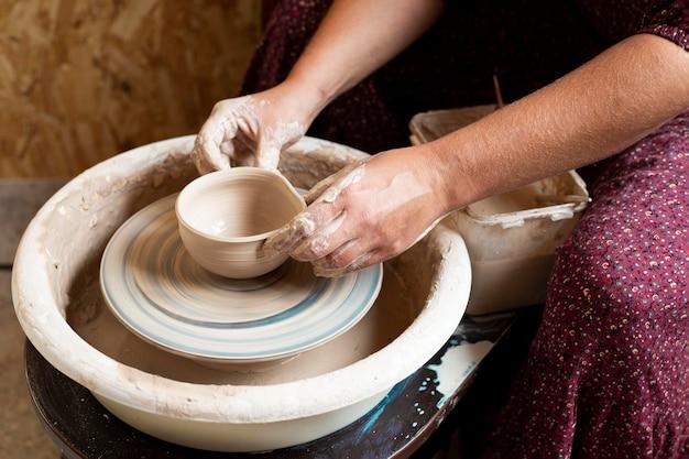 Modelagem em argila em uma roda de oleiro vista elevada