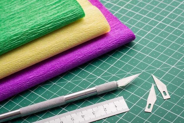 Modelagem. equipamento de papelaria e papel grunge em uma esteira de corte verde