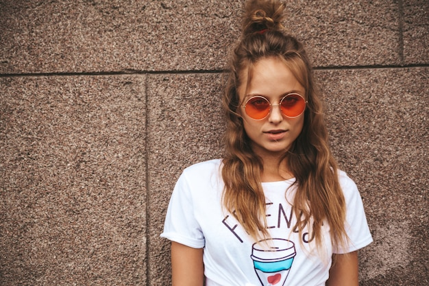 Modelo adolescente bonito loiro bonito em roupas de hipster branco verão posando perto da parede na rua