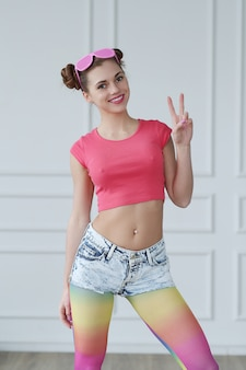 Modelo adolescente em roupas desagradáveis de hippie e meia-calça arco-íris