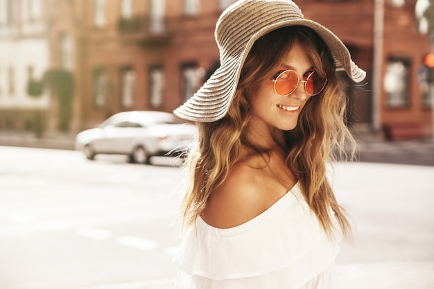 Modelo adolescente loiro sem maquiagem e chapéu de praia grande posando na rua