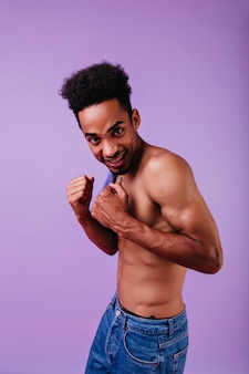 Modelo africano animado posando sem camiseta. negro nu em pé.