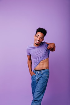 Modelo africano romântico tirando a camiseta. foto interna de rir bonito homem negro.
