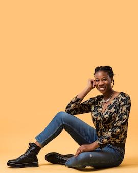 Modelo afro-americano alegre sentado Foto gratuita