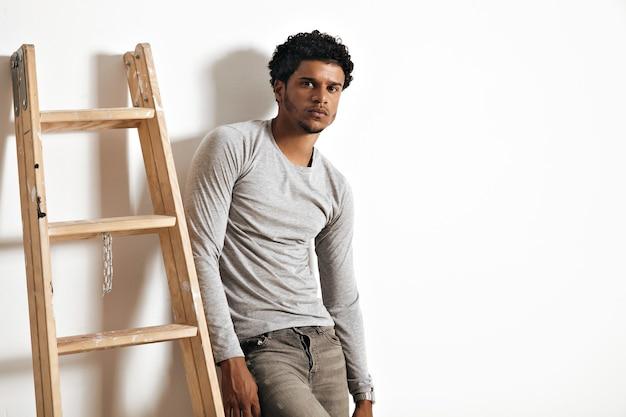 Modelo afro-americano sério e triste com uma camiseta de manga comprida cinza urze e jeans encostado na parede branca ao lado de uma escada de madeira