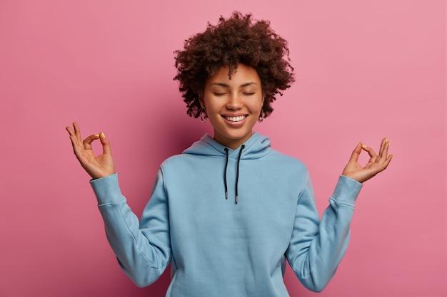 Modelo alegre de pele escura mantendo as mãos em postura zen