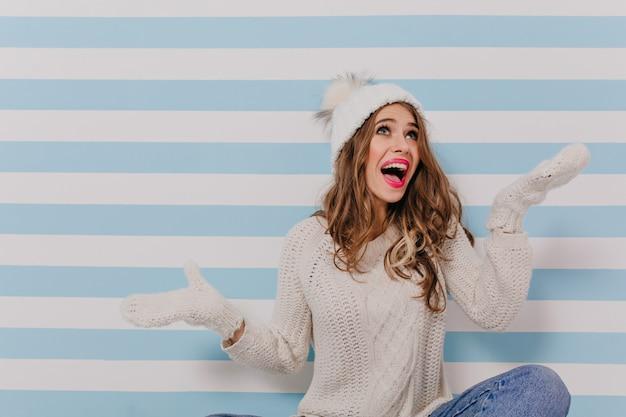 Modelo alegre jovem encaracolado em roupas brancas e jeans azul está sentado no chão e emocionalmente posando para um retrato na parede azul listrada