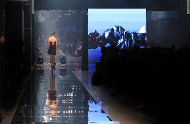 Modelo andar de volta no espelho no desfile de moda