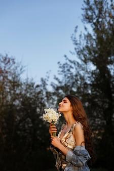Modelo ao sol em uma caminhada no verão. nas mãos de um buquê de flores. espaço borrado. felicidade e um sorriso no seu rosto