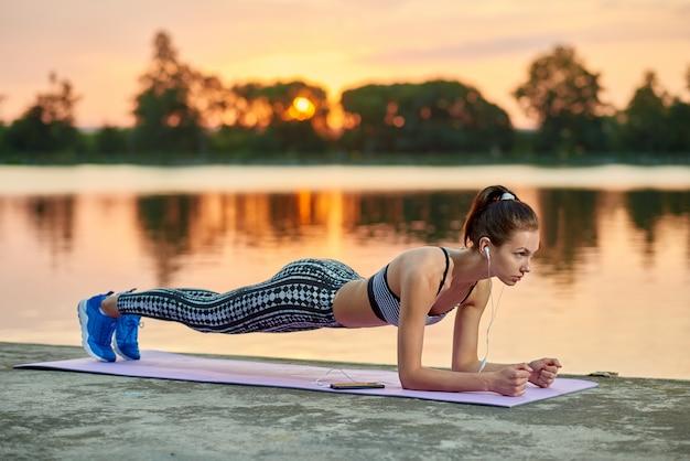Modelo apto que faz o exercício da prancha perto do lago no por do sol. ao ar livre, exercitando-se no ar fresco à noite.