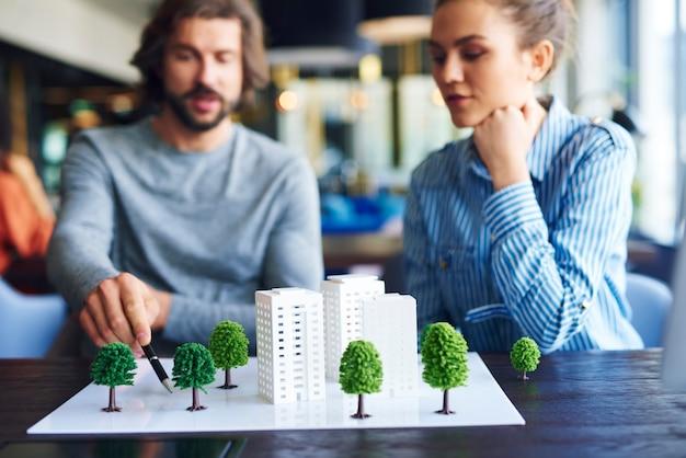 Modelo arquitetônico e arquitetos jovens adultos ao fundo