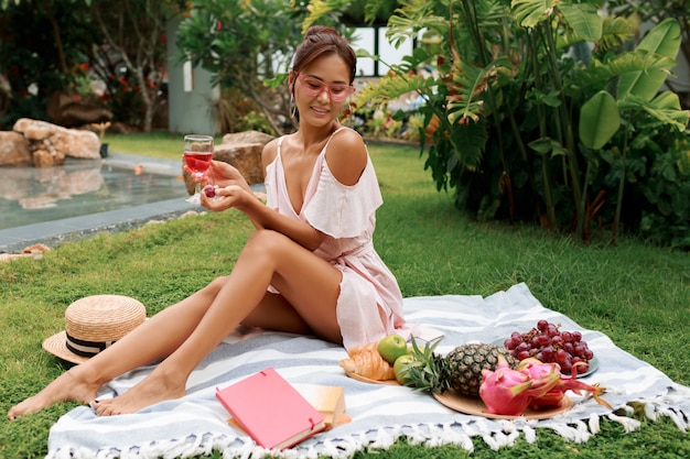 Modelo asiático bastante gracioso sentado no cobertor, bebendo vinho e desfrutando de piquenique de verão no jardim tropical.