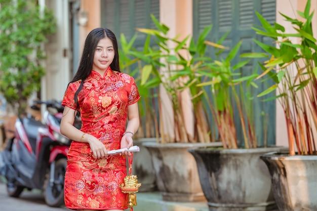Modelo asiático bonito que veste o ano novo chinês tradicional de cheongsam.happy