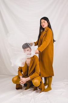 Modelo asiático cobrindo o rosto masculino com tecido transparente