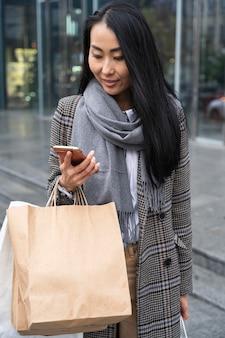 Modelo asiático sorridente carregando sacolas