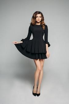 Modelo atraente com cabelos ondulados morena no clássico vestido preto e salto alto.