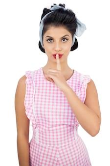 Modelo atraente de cabelo preto posando um dedo na boca