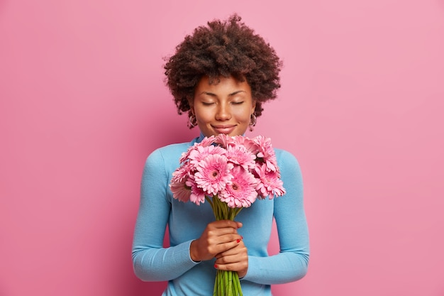 Modelo atraente de pele escura e satisfeita recebe flores como presente, fica com os olhos fechados, desfruta de suas gerberas favoritas,
