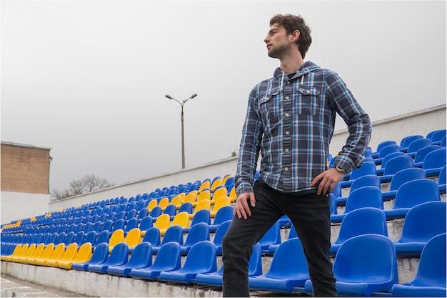 Modelo atraente desportivo jovem de camisa azul, sentado nos assentos do estádio azul após o treinamento, olhando para o campo