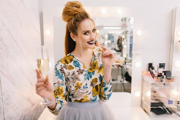 Modelo atraente e elegante com penteado luxuoso e bela maquiagem sorrindo para a câmera em um salão de cabeleireiro com uma taça de champanhe