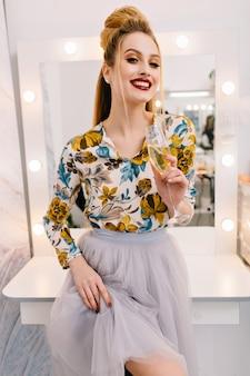 Modelo atraente e estiloso em saia de tule, com penteado luxuoso, linda maquiagem sorrindo para a câmera no salão de cabeleireiro com uma taça de champanhe