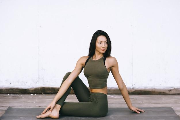 Modelo atraente em pose de ioga em fundo branco em roupas sexuais