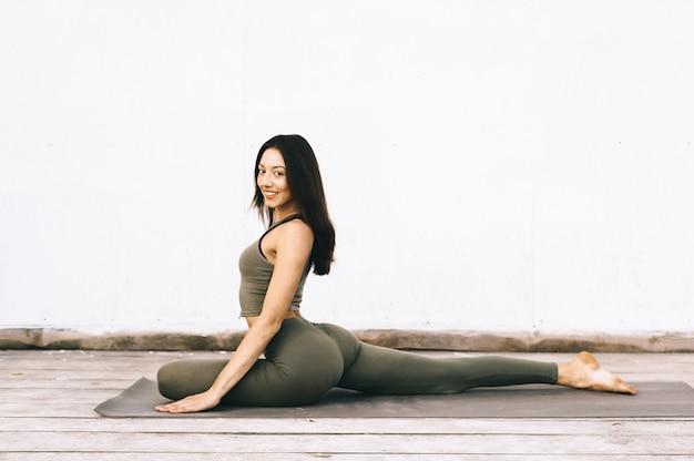 Modelo atraente em pose de ioga em fundo branco
