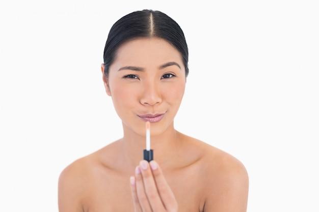Modelo atraente engraçado segurando o brilho labial
