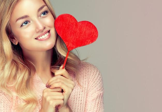 Modelo atraente está segurando um coração simbólico na vara.