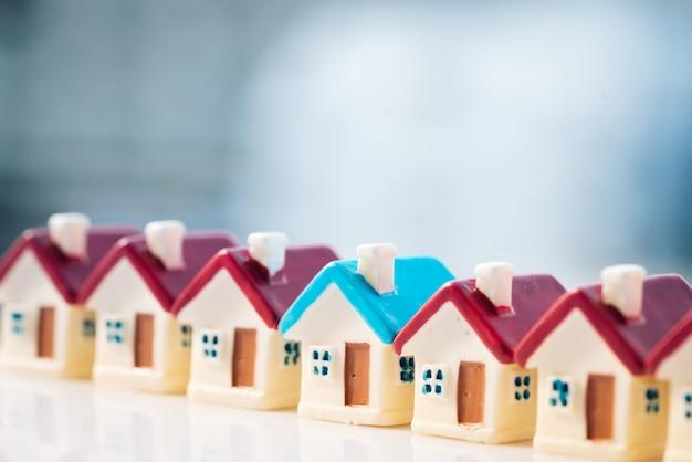 Modelo azul da casa entre a casa vermelha com fundos da cidade.