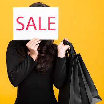 Modelo black friday cobrindo o rosto com um banner de venda