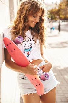 Modelo bonito adolescente sorridente fofo loiro sem maquiagem em roupas de hipster branco verão com skate centavo rosa posando no fundo da rua